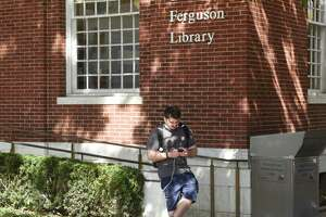 Stamford's Rion Baptist browses on his phone outside Ferguson Library in Stamford, Conn. Sunday, Sept.26, 2021. Thanks to the Connecticut Education Network, the Ferguson Library Downtown branch, Weed branch, and Harry Bennett branch will all have stronger and more reliable Wi-Fi outside of the building, which the library hopes will help bridge the digital divide.