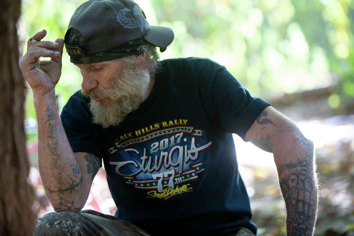 """Poncho, who declined to give his last name, talks Thursday near his camp in San Marcos. Poncho has been unhoused for years and wants a safe place to sleep and live, likening the stress of being unhoused is to """"taking the SAT five times in a row."""""""