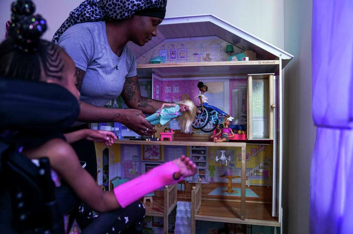 My'onna Hinton and her mother, Brayonna Hinton, play with dolls at their Washington apartment.