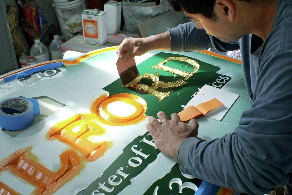 Sign maker Charlie Creller of Branford's Signs by Autografix works on a new sign for Guilford, which are made of high density urethane foam, that looks just like wood. Above, Creller applies gold leaf.