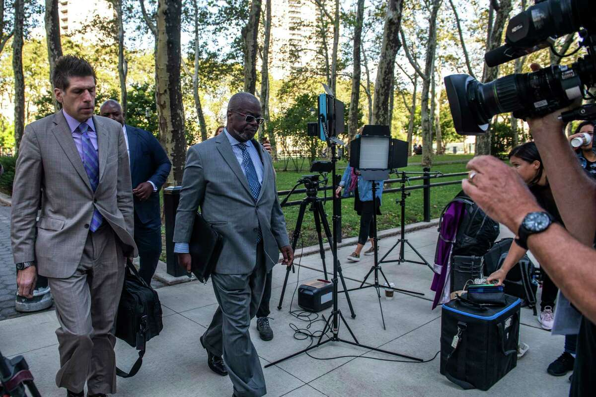 """CORRECTS SPELLING OF DEVERAUX - Attorney Deveraux Cannick, representing R&B star R. Kelly, center, arrives at Brooklyn Federal Court House on Monday, Sept. 27, 2021, in New York. The jury resumed deliberations on Monday at the sex trafficking trial of Kelly. The 54-year-old singer of the smash hit """"I Believe I Can Fly"""" has denied any wrongdoing."""