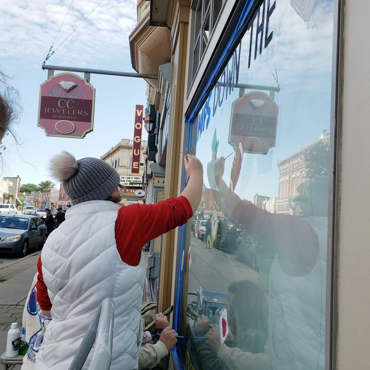 Flynn Anderson works on the Manistee High School freshmen class homecoming window art on Saturday on River Street.