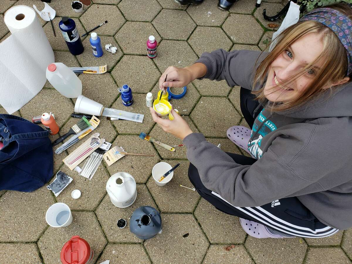 Callie Ronning prepares a cup of paint for the Manistee High School senior class homecoming art project at the Vogue Theatre on Sunday.