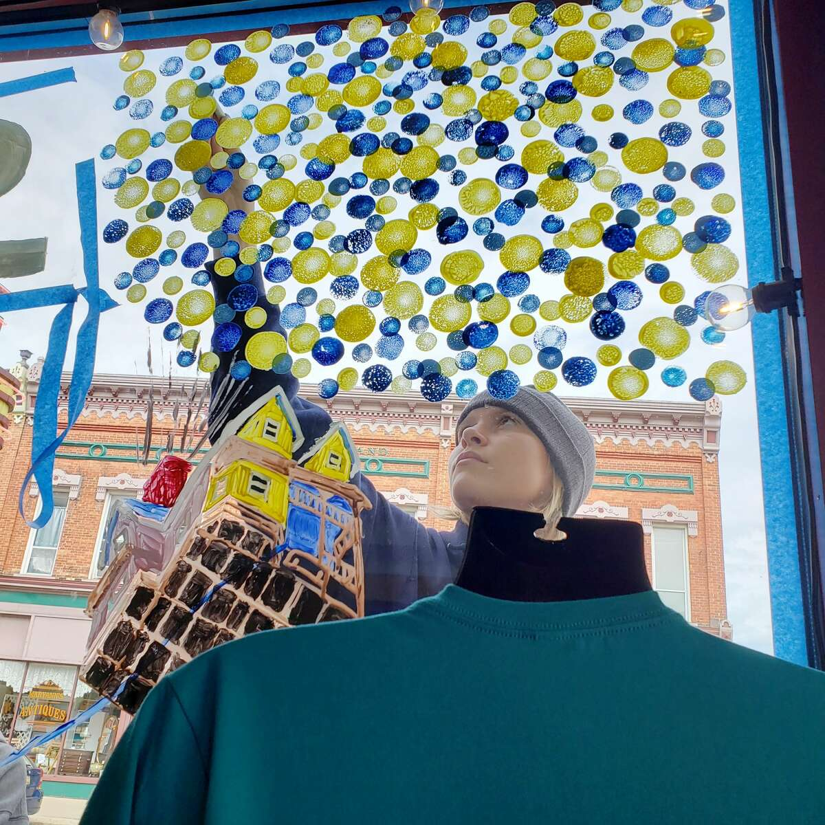 """Raegan Codden paints balloons in reference to the movie """"Up""""on the Vogue Theatre's window on River Street for the Manistee High School senior class homecoming art project."""