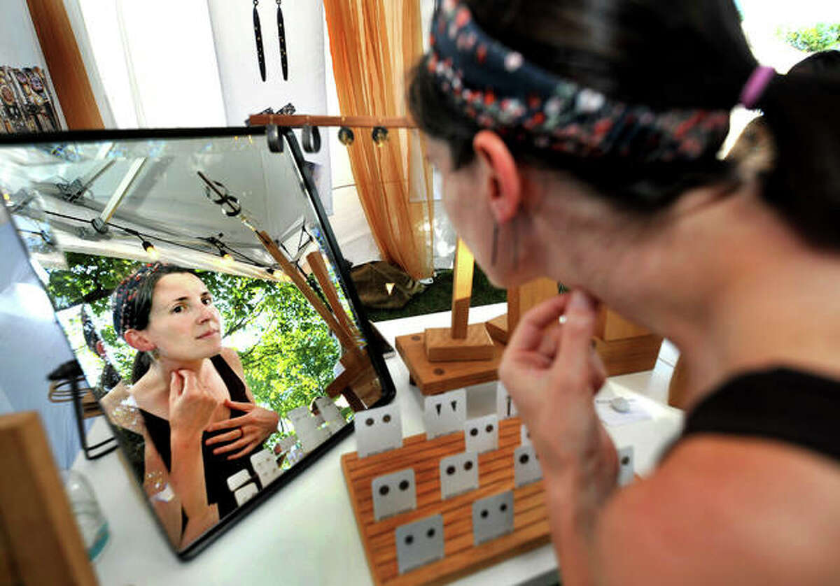 Alma Carver of Edwardsville looks at earrings she is interested in on her in a mirror at the tent of Rocky Pardo Jewelry during the Edwardsville Art Fair in City Park Saturday.
