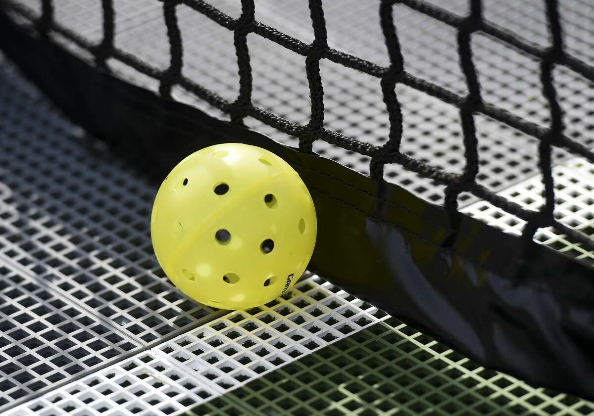 A pickleball on the court next to the net.