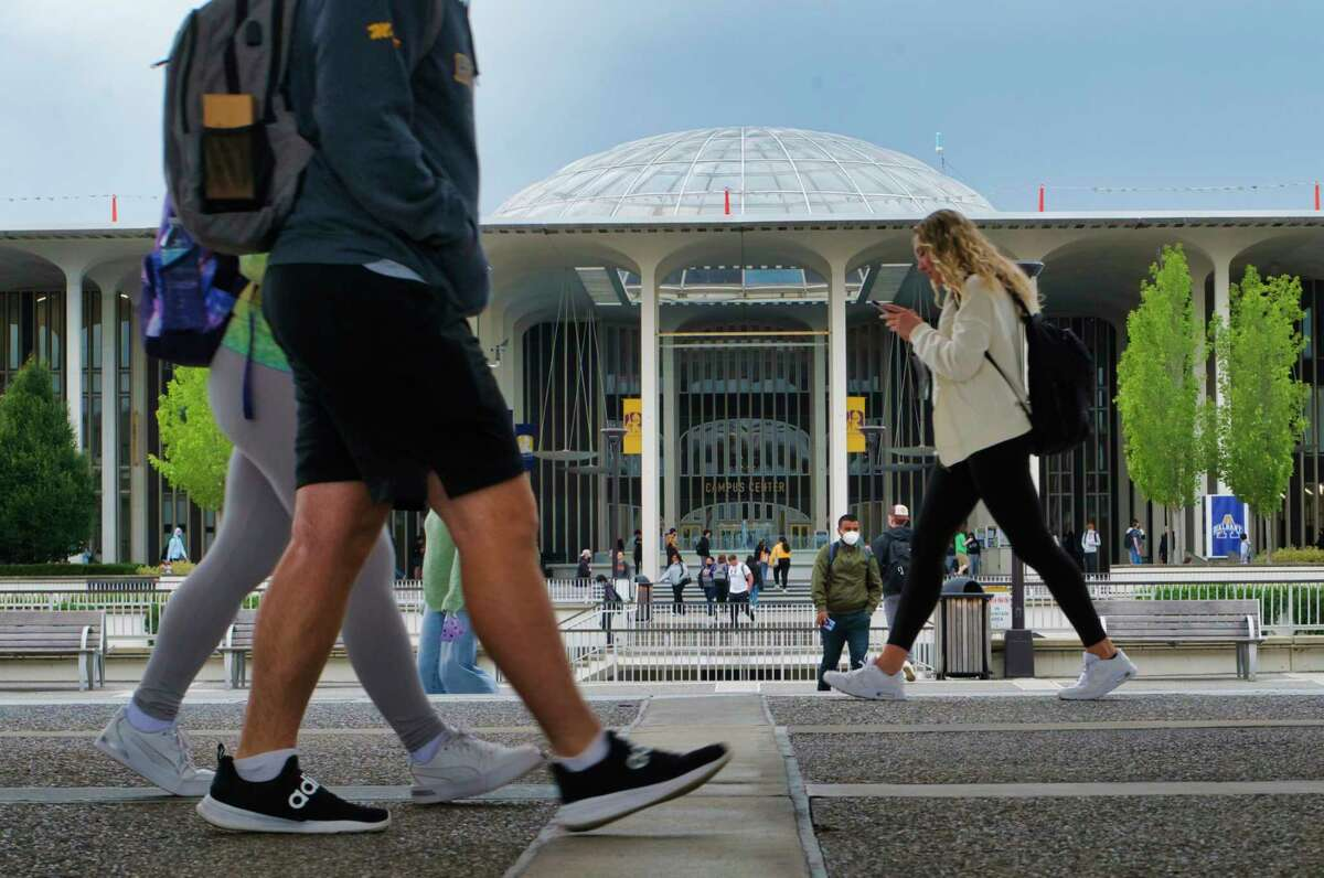 Students make their way between classes at the University at Albany on Monday, Sept. 27, 2021, in Albany, N.Y. SUNY is poised to raise tuition for out-of-state students. The Board of Trustees will consider it at a meeting Sept. 29, 2021.