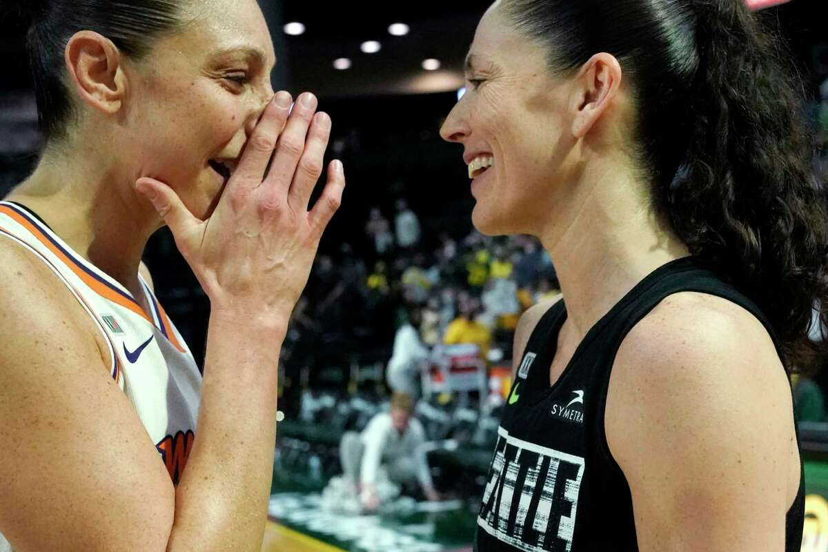 Phoenix Mercury's Diana Taurasi, left, talks with Seattle Storm's Sue Bird after the Mercury defeated the Storm in the second round of the WNBA basketball playoffs Sunday, Sept. 26, 2021, in Everett, Wash. (AP Photo/Elaine Thompson)