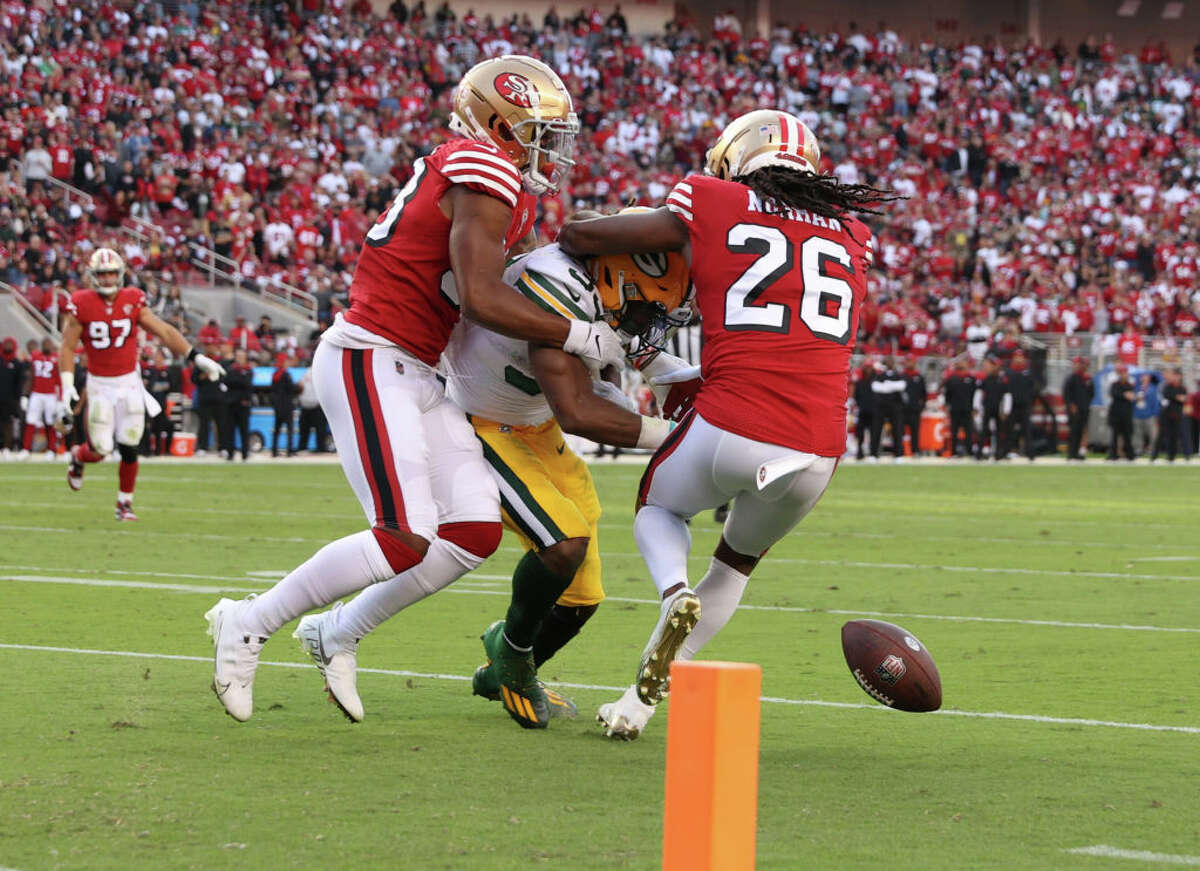Josh Norman, right, and Deommodore Lenoir of the San Francisco 49ers force a fumble by Aaron Jones of the Green Bay Packers during the second quarter in the game at Levi's Stadium on Sept. 26, 2021, in Santa Clara, Calif.
