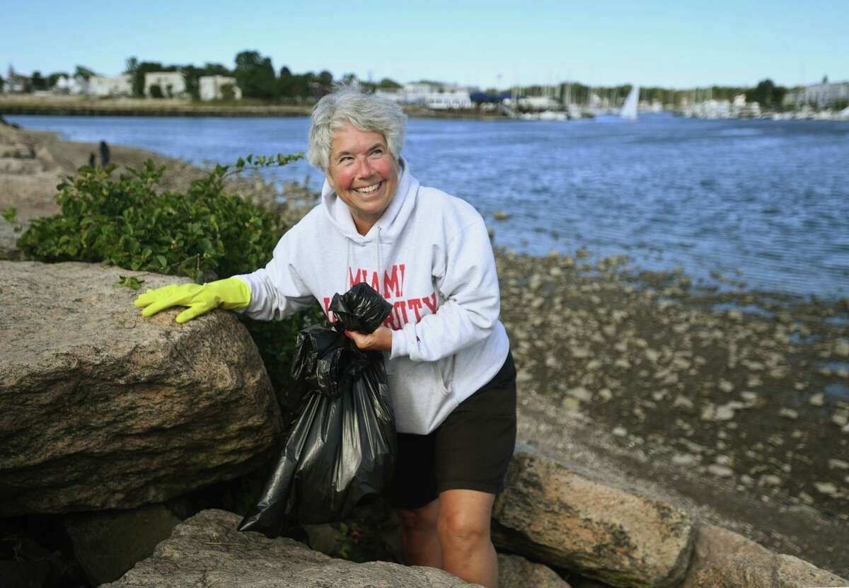 Robbie Silver, of Milford, cleans trash from a jetty at the mouth of Milford Harbor during a beach clean-up, organized by State Rep. Kathy Kennedy, at Gulf Beach in Milford, Conn. on Sunday, September 26, 20i21.