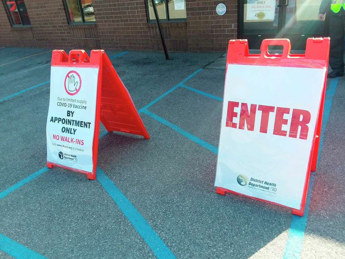 Signs direct people to where to get a COVID-19 vaccine. (File Photo)