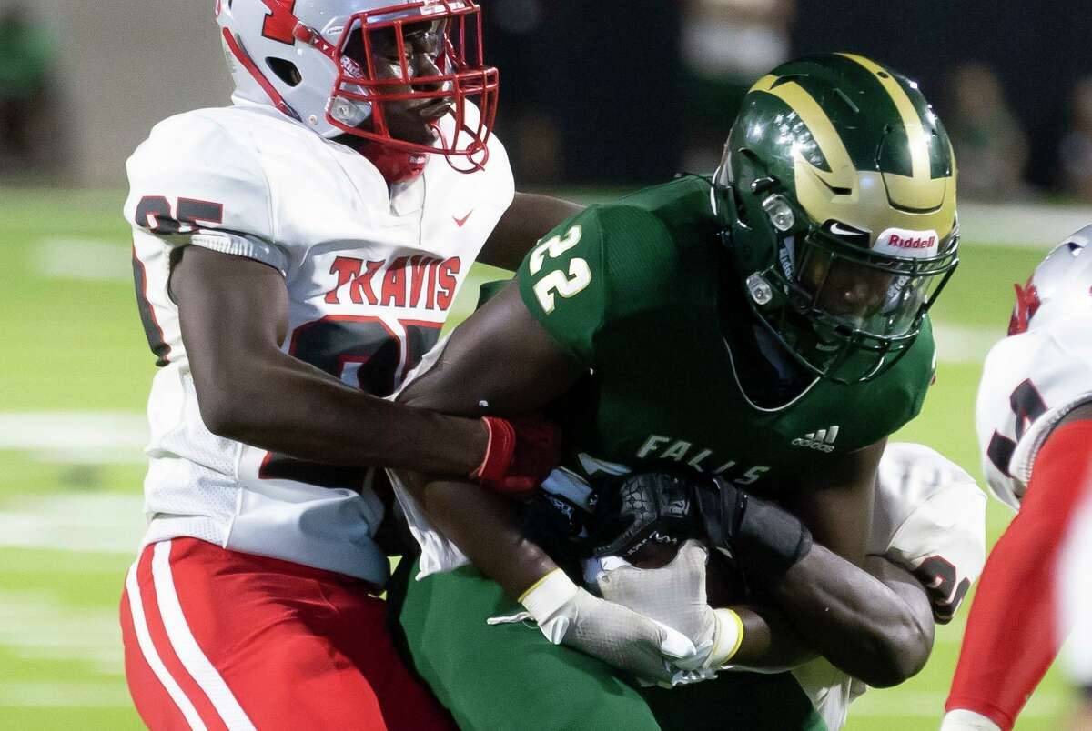 Cypress Falls running back Trey Morris (22) guards the ball as he's taken down by Travis linebacker Isreal Akinlabi (25) during the third quarter of a non-district football game at Cy-Fair FCU Stadium, Saturday, Sept. 11, 2021, in Cypress.