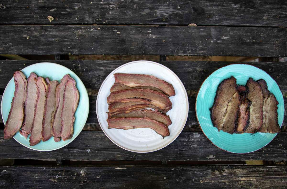 Pre-cooked brisket from H-E-B Smokehouse, left, Pruski's Market, center, and True Texas BBQ, right, are seen on display at Chuck's Food Shack.