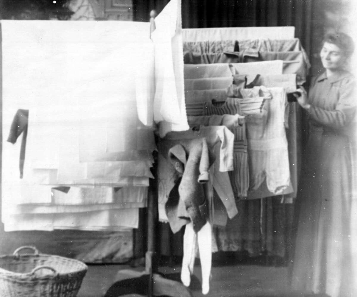 By September 1913, after some changes were made to the original device and another patent issued, Stacy Thompson and H.K. Randall decided to open a small factory in Manistee that would be able to produce the clothes racks. This photo shows a demonstration of aclothes-dryingdrying rack. The photo was taken in Feb. 1919. (Manistee County Historical Museum)