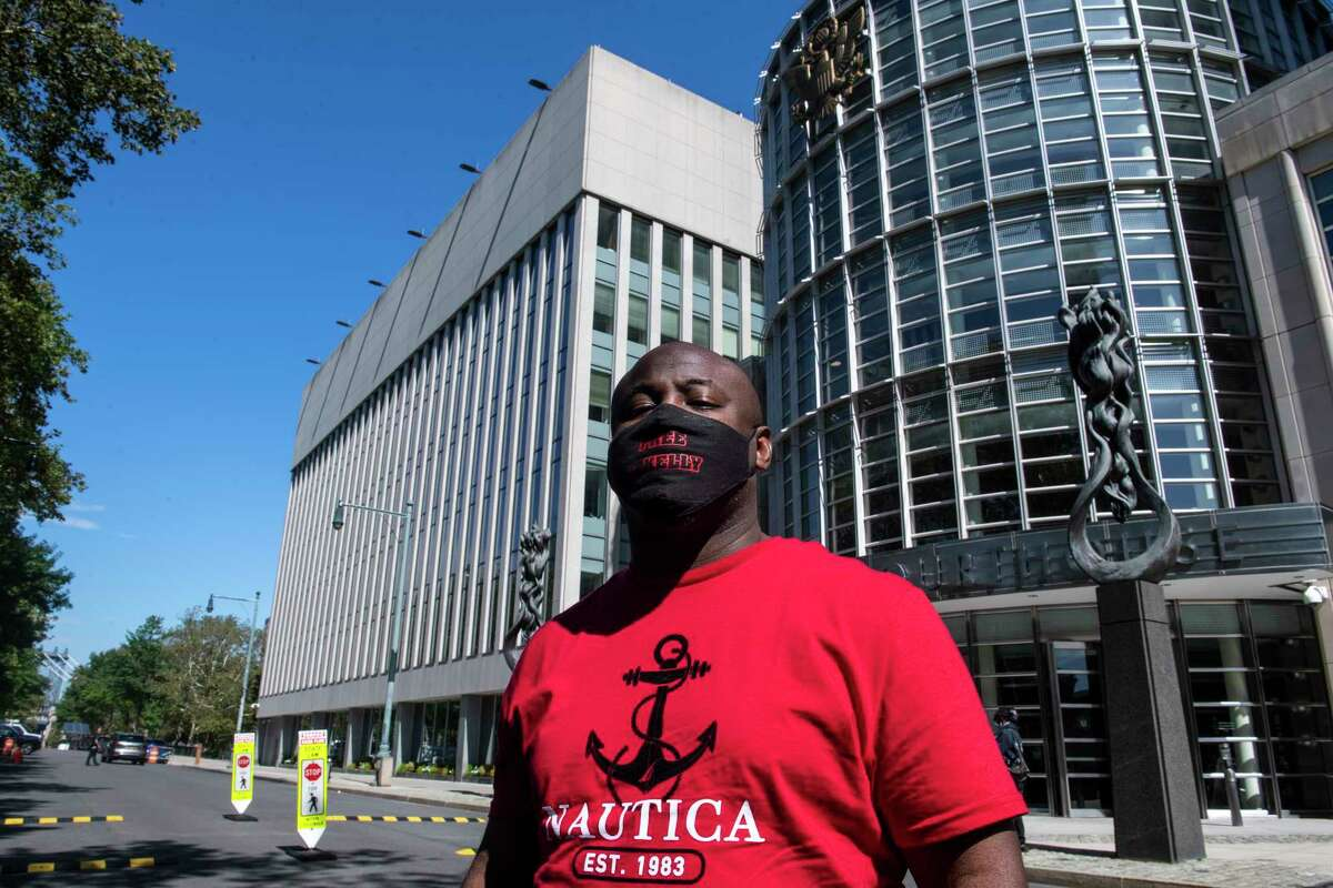 """An unidentified supporter of R&B singer R. Kelly, wears a mask reading """"Free R. Kelly"""" outside Brooklyn Federal Court House on Monday, Sept. 27, 2021, in New York. The 54-year-old Kelly, perhaps best known for the 1996 smash hit """"I Believe I Can Fly, """" has pleaded not guilty to racketeering charges accusing him of sexually abusing women, girls and boys for more than two decades. ."""