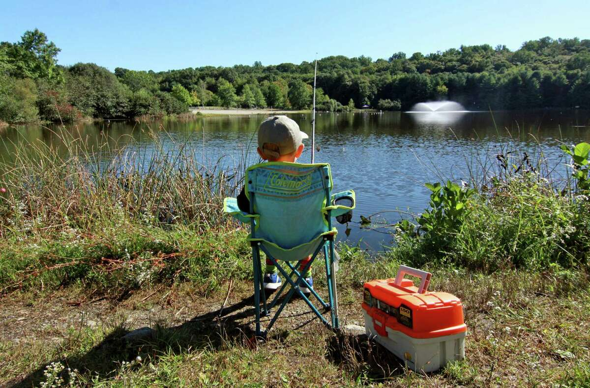Brody Boshell, 6, Newtown, sits at the edge of Great Hollow Lake waiting for a bite during the American Legion District 3's 1st Annual Children's Fishing Derby in Monroe, Conn., on Saturday September 25, 2021.