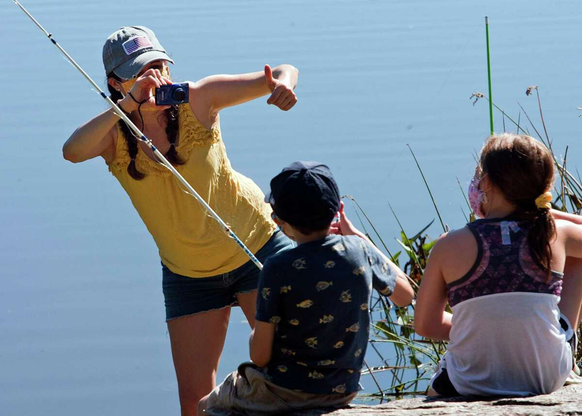 Lisa Richard, of Naugatuck, snaps a picture of her son Brooks, 8, and his friend Katelynn Stanton, 7, of Shelton, at right, during American Legion District 3's 1st Annual Children's Fishing Derby at Great Hollow Lake in Monroe, Conn., on Saturday September 25, 2021.