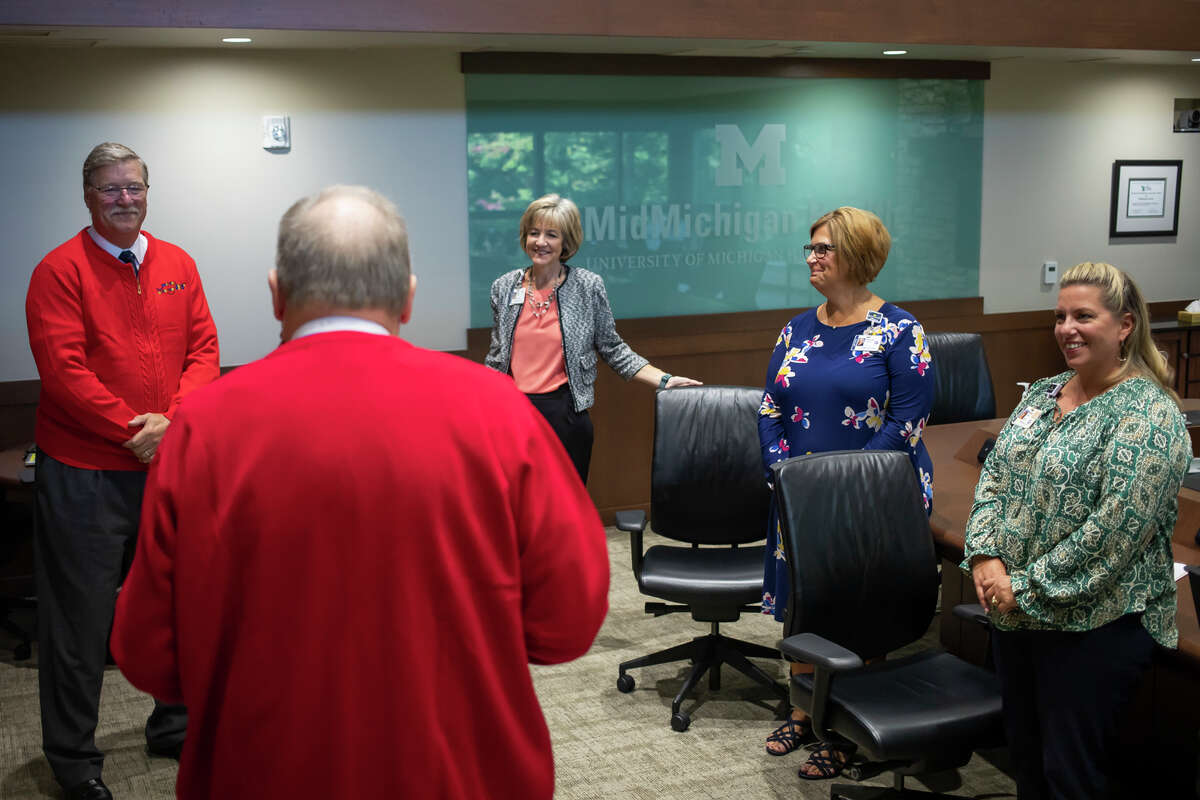 """The Rev. Wallace """"Wally"""" Mayton, foreground, shares words of encouragement with, from left, MidMichigan Health executives Greg Rogers, Mary Greeley, Denise O'Keefe and Millie Jezior while accompanying staff from Midland's Open Door in dropping off coffee and treats at MidMichigan Medical Center - Midland as part of Neighboring Week Monday, Sept. 27, 2021. (Katy Kildee/kkildee@mdn.net)"""