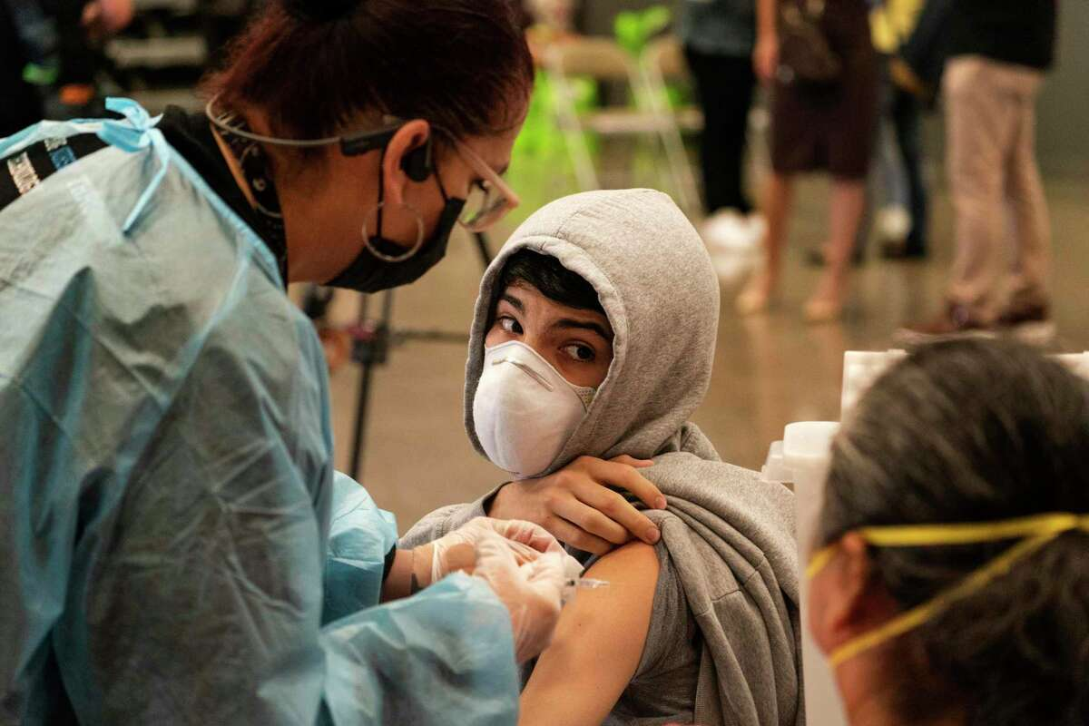 A student looks back at his mother as he is vaccinated at a clinic for students 12 and older in San Pedro (Los Angeles County). The surge is subsiding in California.