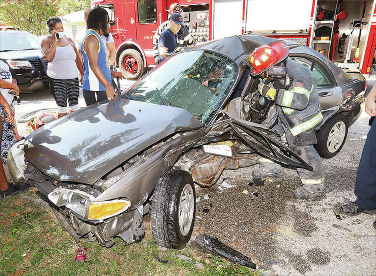 Firefighters use a hydraulic rescue tool Monday to free a driver with a pinned leg when a Ford Escort and a Jaguar XF collided in the 1200 block of Central Avenue in Alton. The driver of the Escort was taken to St. Anthony's Medical Center and transfered by helicopter ambulance to a trauma center in St. Louis.