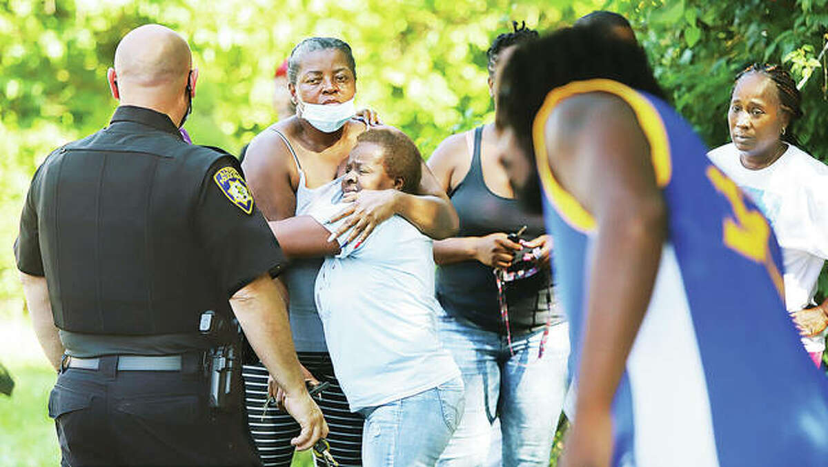 A large, concerned crowd of neighbors, friends and family gathered to watch rescue efforts Monday to free the driver of a Ford Escort involved in a crash in the 1200 block of Central Avenue in Alton.