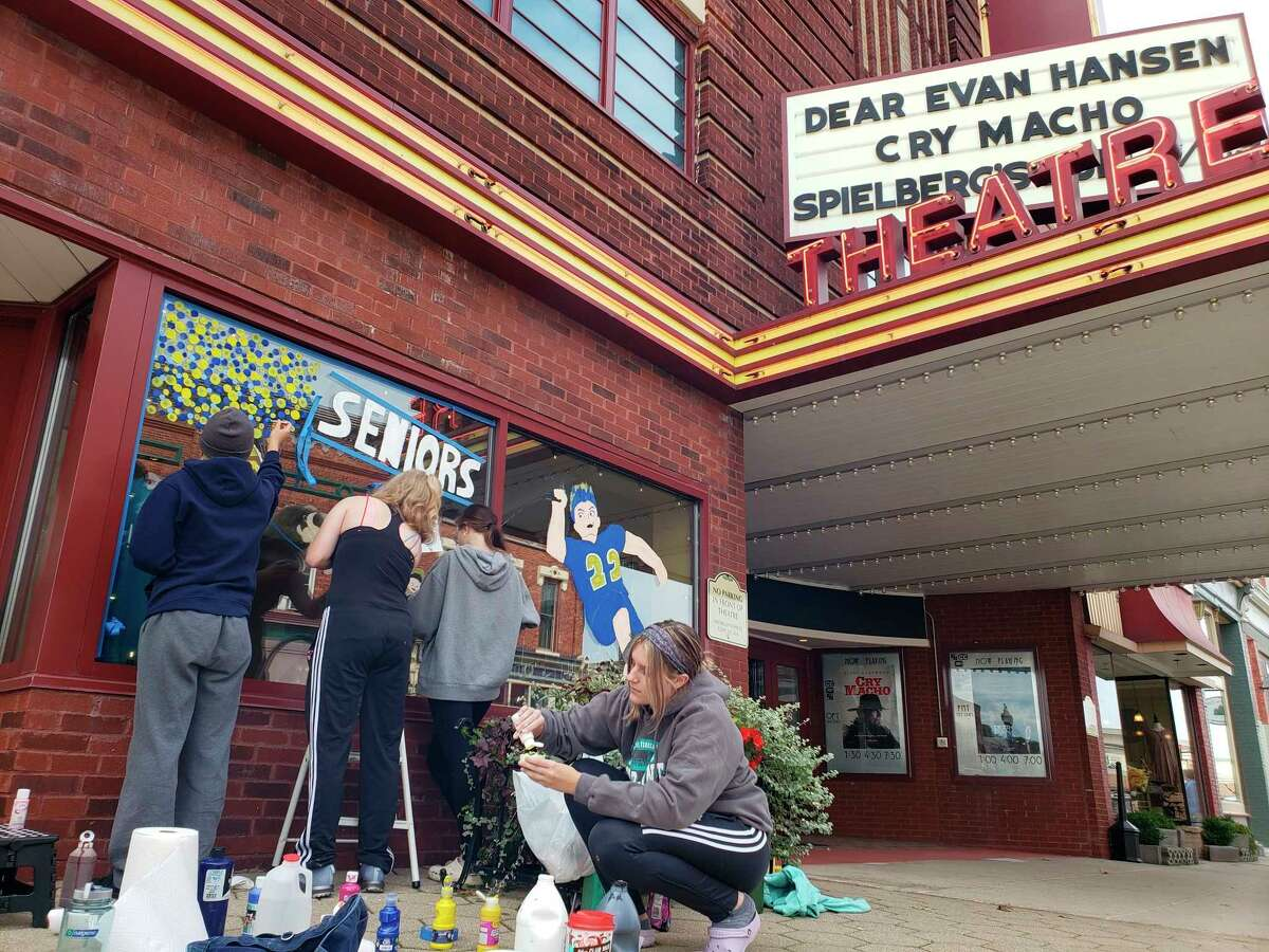 Manistee High School seniorspaint the Vogue Theatre's window on Sunday afternoon, an annual homecoming tradition. (Arielle Breen/News Advocate)