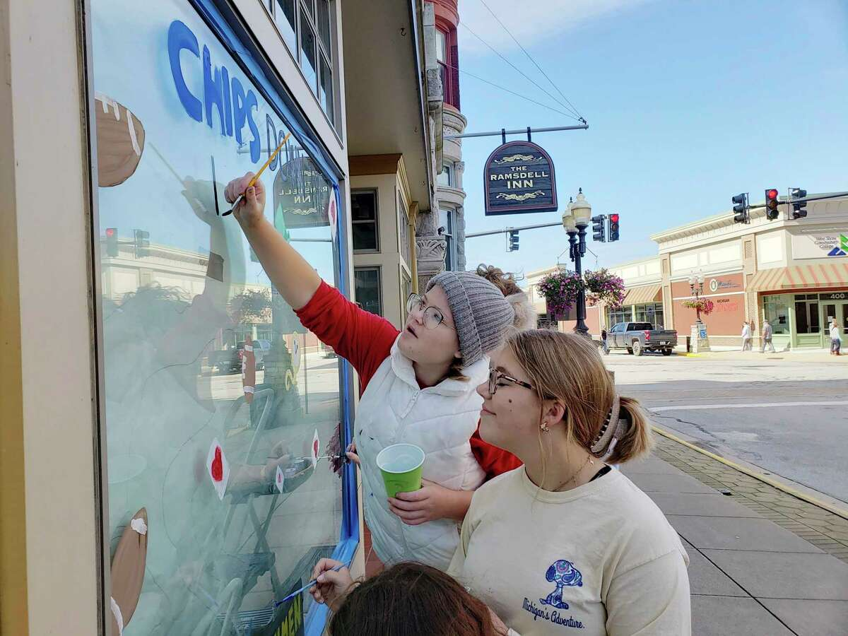 Kaylee Loper (front) and Flynn Andersonwork on the Manistee High School freshmen class homecoming window art on Saturday on River Street. (Arielle Breen/News Advocate)