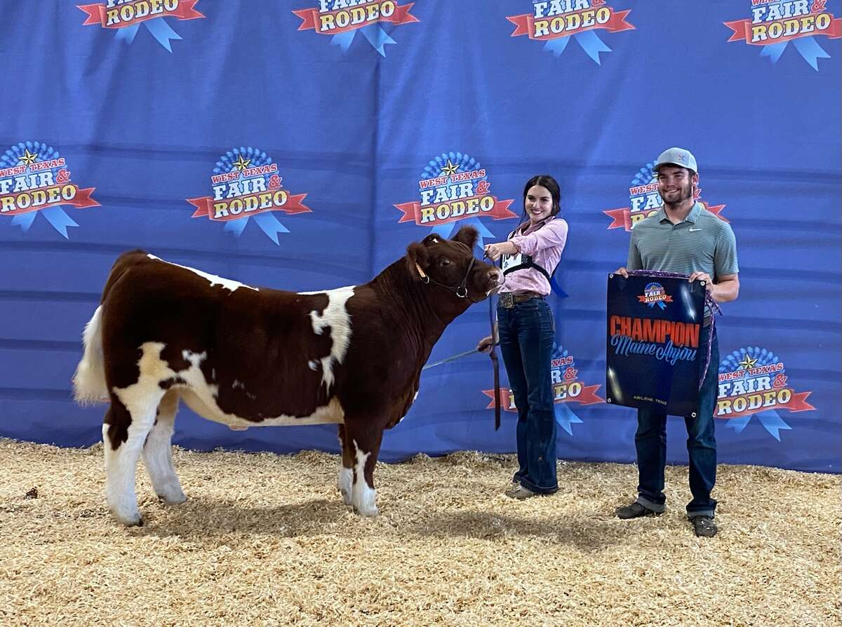 Cassie Jo Bennett and her brother Colt stand with the champion with the Main Anjou breed at the West Texas Fair in Abilene.