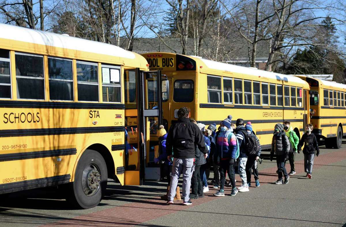 Students board a bus in the Riverside section of Greenwich, Conn. Tuesday, March 2, 2021.