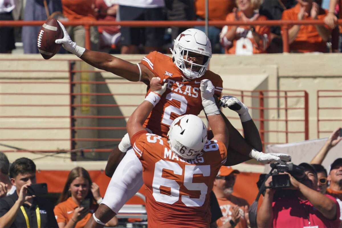 Texas running back Roschon Johnson (2) celebrates his touchdown run against Texas Tech with Jake Majors (65) during the first half of an NCAA college football game on Saturday, Sept. 25, 2021, in Austin, Texas.