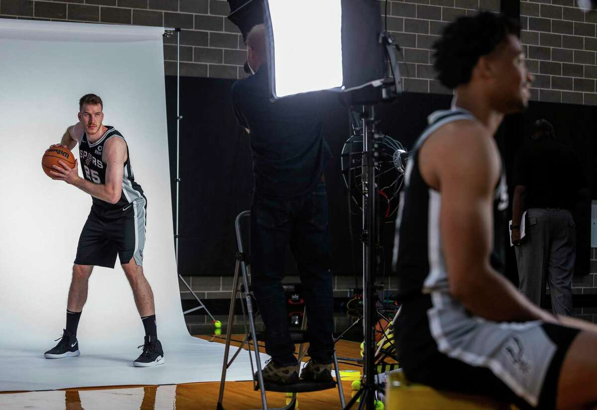 Spurs guard Jakob Poeltl, left, poses for photos Monday, Sept. 27, 2021 at the Spurs practice facility during the team's media day while teammate Keldon Johnson, right, does an interview.