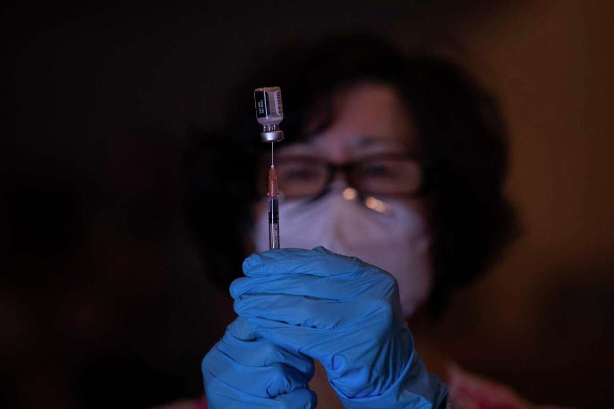 Rosa Cheng, a clinical registered nurse lead with Visit Healthcare, a San Francisco Vaccination Clinic, draws a Pfizer vaccine into a syringe at a new vaccination site at Balboa High School in San Francisco , Calif.