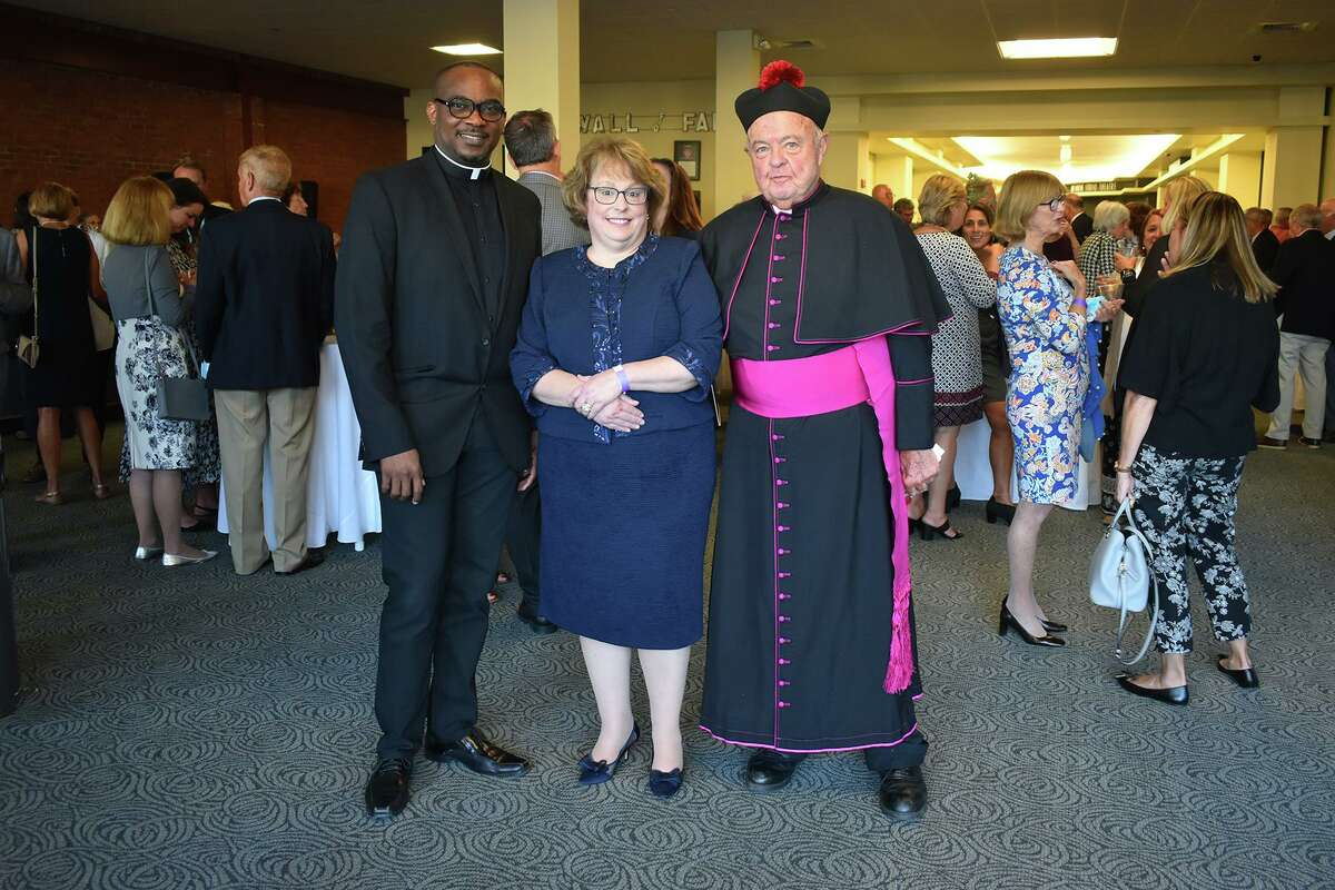 Msgr. Robert Tucker was honored Sept. 26 at the Nancy Marine Studio Theater at the Warner Theatre in Torrington. From left are the Rev. Emmanuel Ihemedu, pastor of St. John Paul the Great church and school; school board president Susan Cook and Tucker.