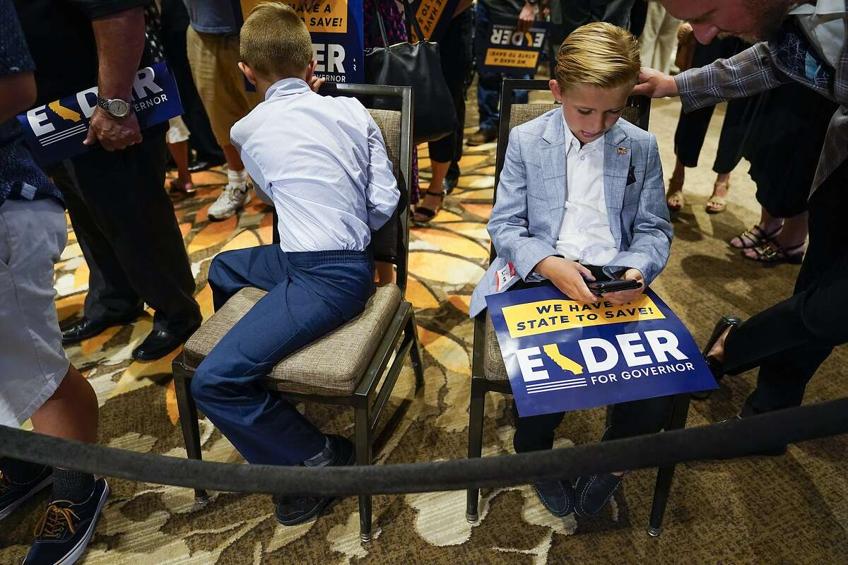 Two boys and other supporters of republican conservative radio show host Larry Elder wait for results after polls close for the California gubernatorial recall election Tuesday, Sept. 14, 2021, in Costa Mesa, Calif. The rare, late-summer election, which challenged California Governor Gavin Newsom, has emerged as a national battlefront on issues from COVID-19 restrictions to climate change. (AP Photo/Ashley Landis)