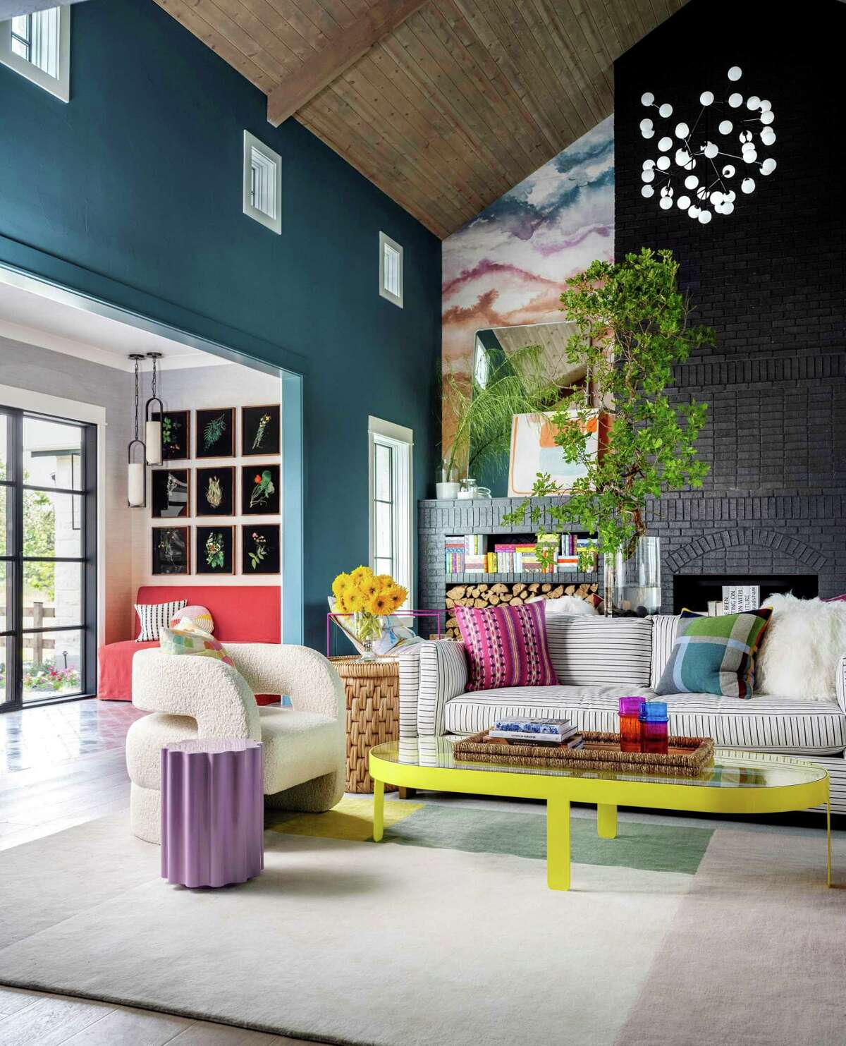 The entryway and living room of the 2021 Whole Home Concept House was designed by Emilie Munroe of the San Francisco firm Studio Munroe. The massive space has a 20-foot-high vaulted ceiling and an inky black brick fireplace flanked by dramatic multicolored wall coverings.