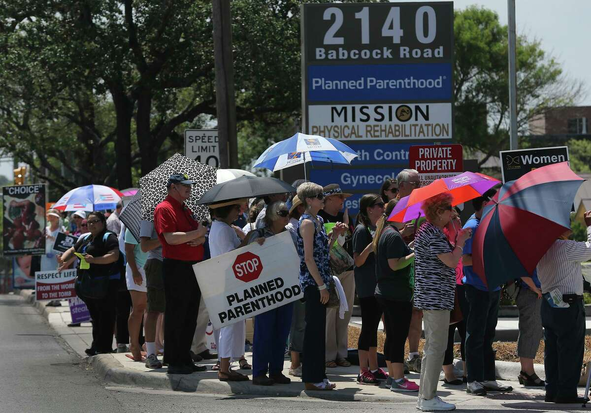 """People line up Tuesday July 28, 2015 at 2140 Babcock Road in front of Planned Parenthood during a """"Women Betrayed Rally."""" Protesters at the event were calling on government officials to investigate and defund Planned Parenthood."""