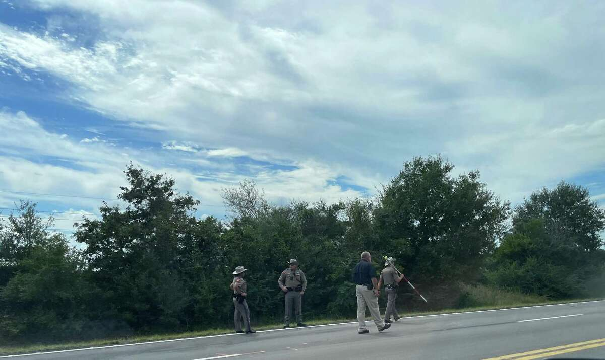 Investigators with the Waller Police Department and Texas Department of Public Safety do measurements for a crash scene reconstruction along U.S. 290 Business in Waller on Sept. 27, 2021. On Sept. 25, a teenager driving a pickup truck struck and injured six bicyclists on a training ride.