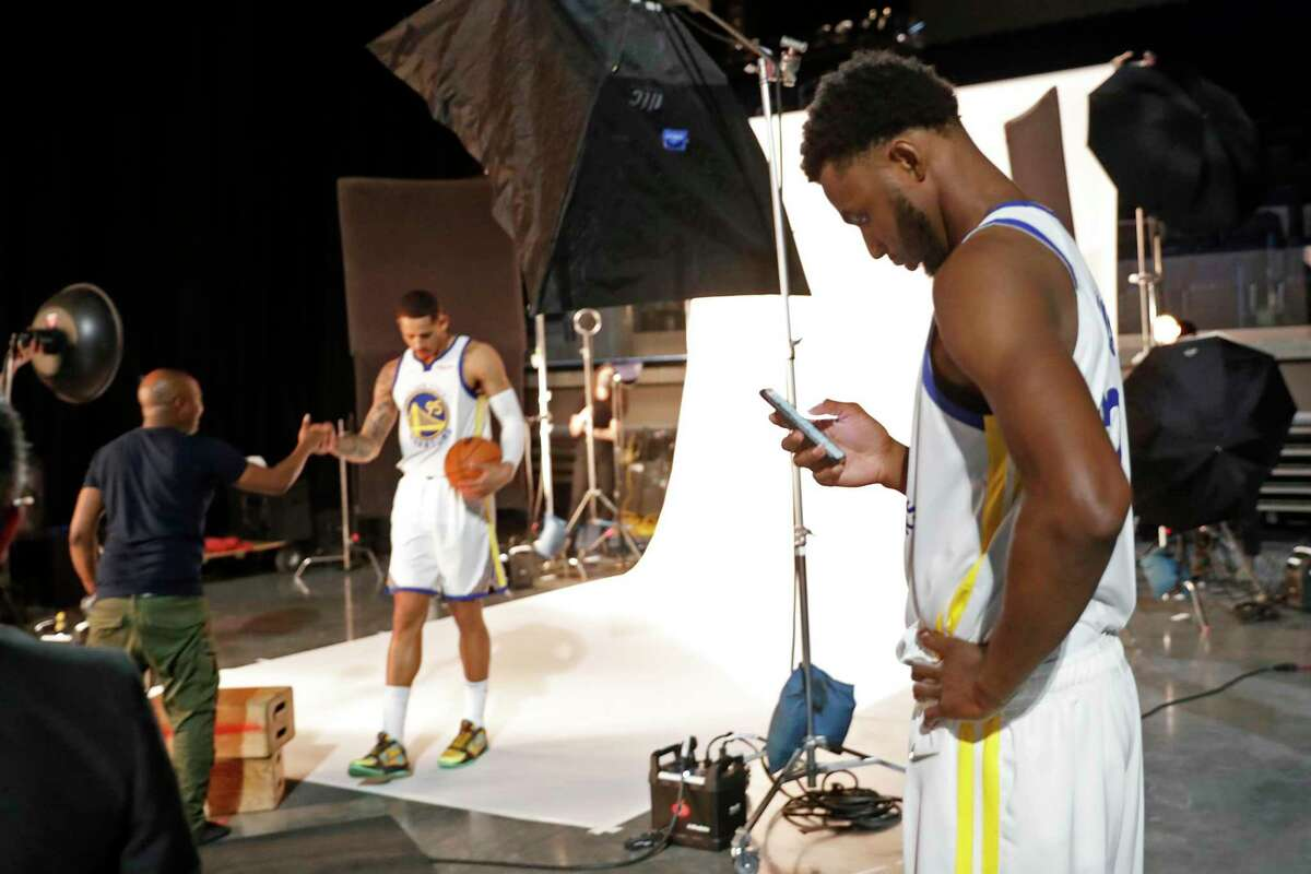 Golden State Warriors' Andrew Wiggins looks ta his phone as Juan Toscano-Anderson finishes up a session during media day at Chase Center in San Francisco, CA on Monday, September 27, 2021.