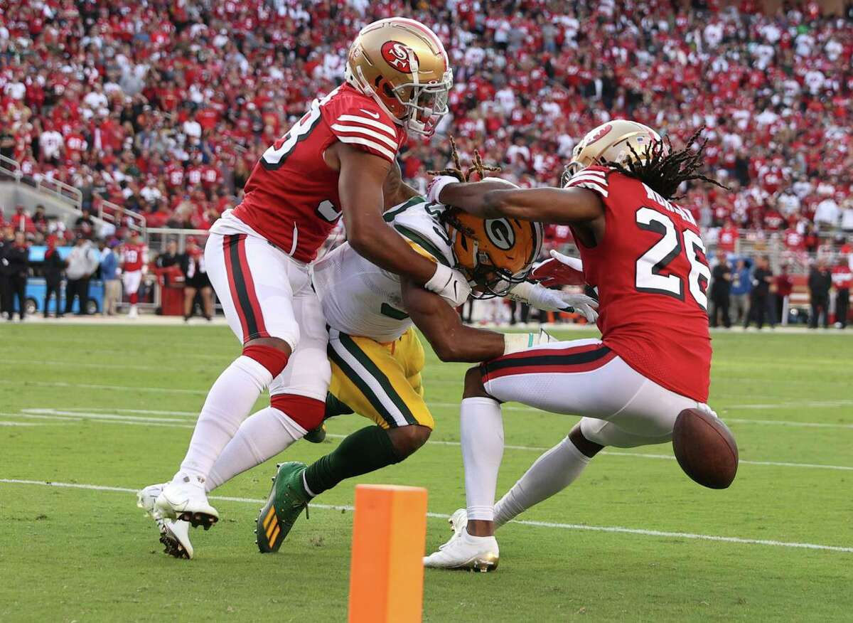 Niners Josh Norman and Deommodore Lenoir force Aaron Jones into a fumble that went out of bounds during the second quarter of Sunday's loss to Green Bay.