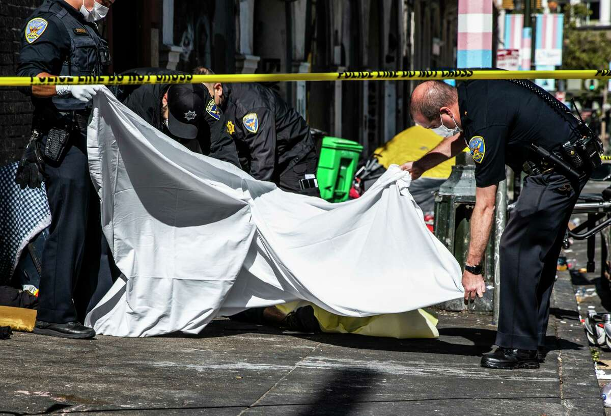 San Francisco police officers hold a body bag as members of the medical examiner's team work to transfer the body of a likely overdose victim near the corner of Golden Gate Avenue and Jones Street in San Francisco.