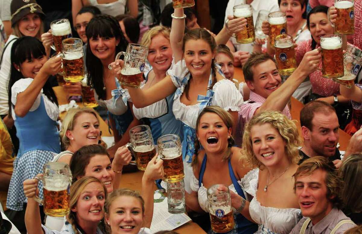 MUNICH, GERMANY - SEPTEMBER 18: Visitors of the Oktoberfest toast with beer mugs during the opening day of the Oktoberfest at Theresienwiese on September 18, 2010 in Munich, Germany. 2010 marks the 200th anniversary of Oktoberfest.The Oktoberfest tradition started in 1810 to celebrate the October 12th marriage of Bavarian Crown Prince Ludwig to the Saxon-Hildburghausen Princess Therese. The citizens of Munich were invited to join in the festivities which were held over five days on the fields in front of the city gates. The main event of the original Oktoberfest was a horse race. The world's biggest beer festival will last this year from September 18 to October 4. (Photo by Alexandra Beier/Getty Images)