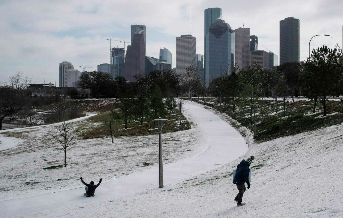 Chris Martinez, right, looks back at a man sliding down a hill as a winter storm hits Houston on Monday, Feb. 15, 2021, at Buffalo Bayou Park in Houston.