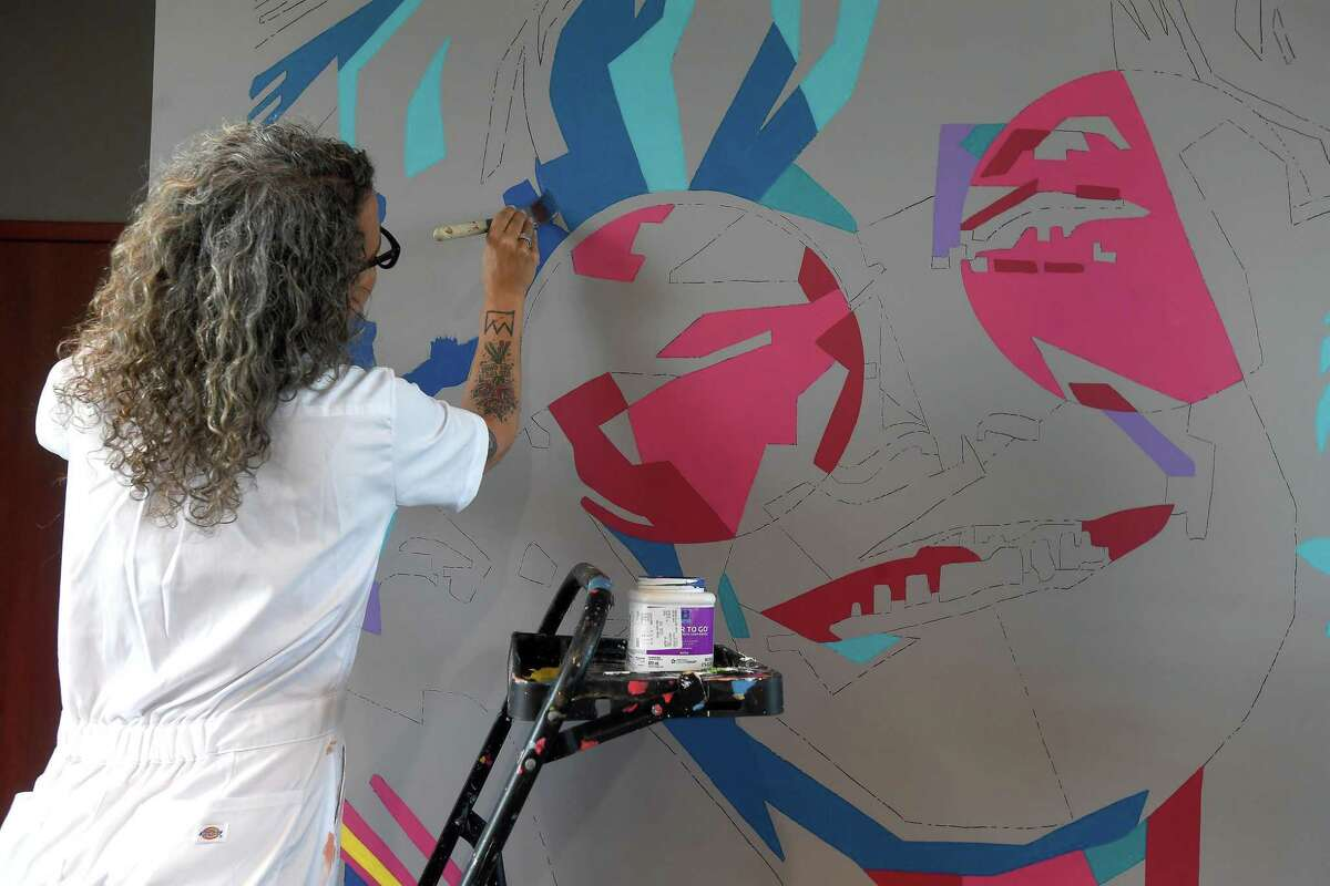 """Artist Kimberly Brown starts work on a wall-length Janis Joplin mural at the Ben J. Rogers Regional Visitors Center Wednesday. The piece will fill the space next to the jukebox, where a display was destroyed during flooding from Imelda. Center Director Kathi Hughes said they chose to feature Janis Joplin not only because she is part of the rich musical history of Southeast Texas, but because """"people are fascinated by Janis. So many people, especially international travelers, want to know about her"""" and where she grew up. Joplin and Spindletop are among the top tourist draws, Hughes said. The public is invited to watch Brown's work in progress as it continues Thursday. Photo made Wednesday, September 22, 2021 Kim Brent/The Enterprise"""