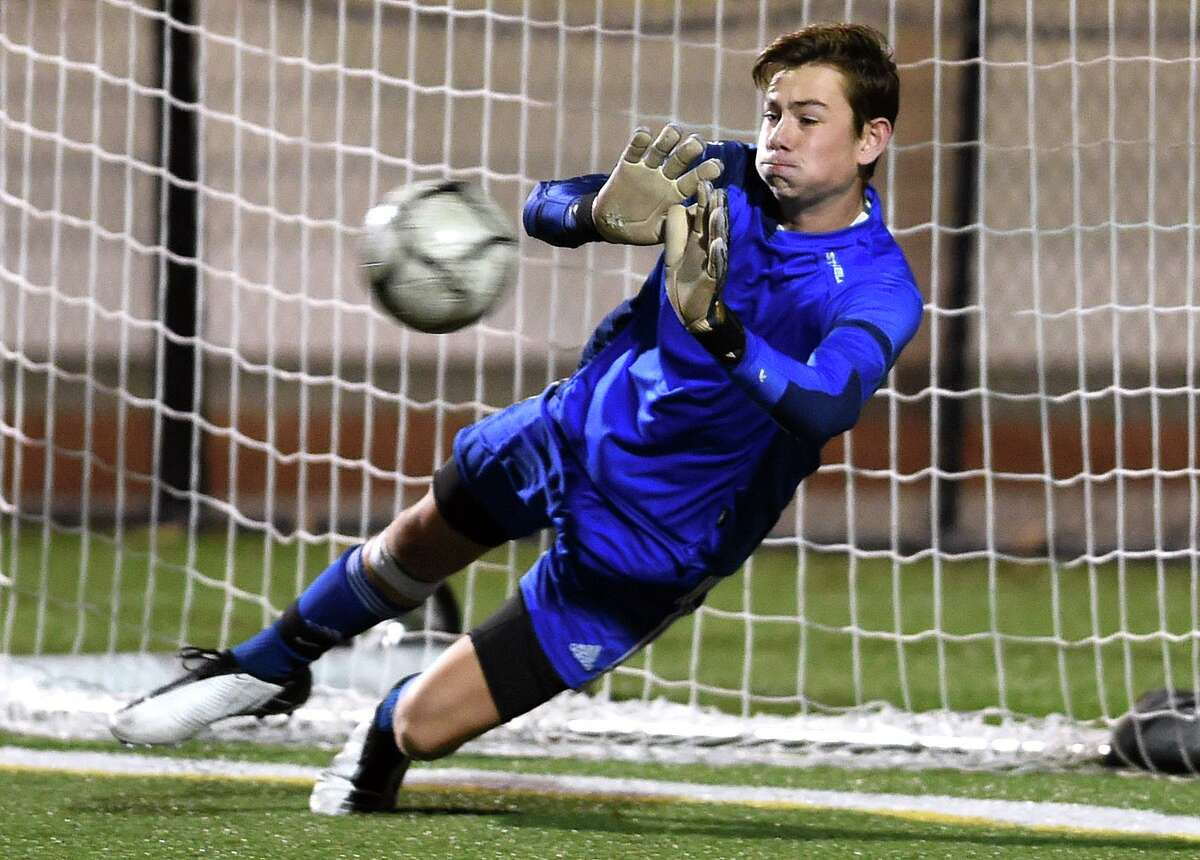 Guilford goalie Justin Hess blocks a penalty shot in the second half of the SCC Championship in Madison against Hand in 2020.