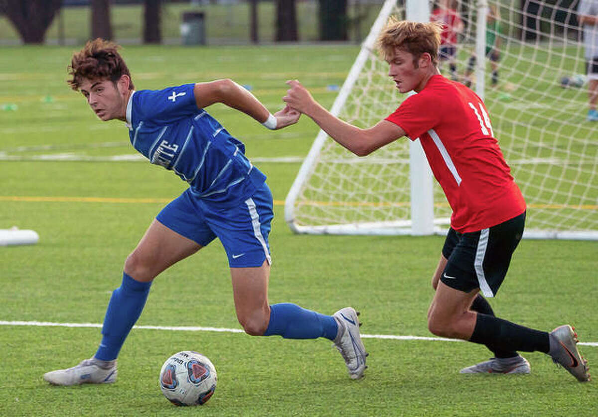 Marquette's Myles Paniagua (7) tangles with Alton High School's James Standeback (14) Monday night during Marquette's 3-1 victory at Gordon Moore Park.