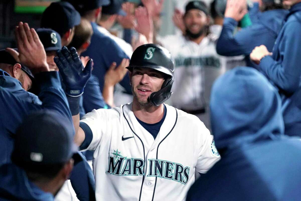 Seattle Mariners' Mitch Haniger is congratulated by teammates on his three-run home run against the Oakland Athletics in the sixth inning of a baseball game Monday, Sept. 27, 2021, in Seattle. Haninger hit another three-run homer in the fourth inning. (AP Photo/Elaine Thompson)