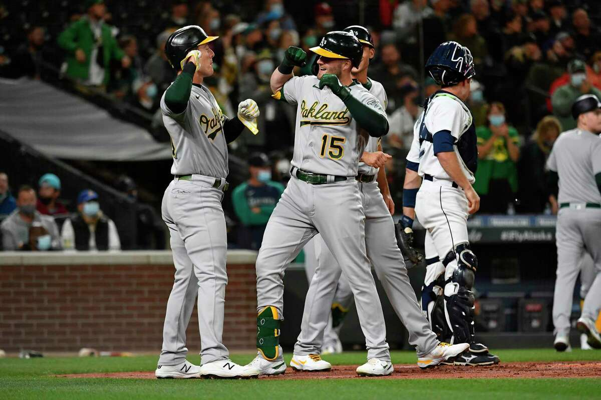 SEATTLE, WASHINGTON - SEPTEMBER 27: Seth Brown #15 of the Oakland Athletics celebrates with Matt Olson #28 and Mark Canha #20 after hitting a home run during the first inning against the Seattle Mariners at T-Mobile Park on September 27, 2021 in Seattle, Washington. (Photo by Alika Jenner/Getty Images)