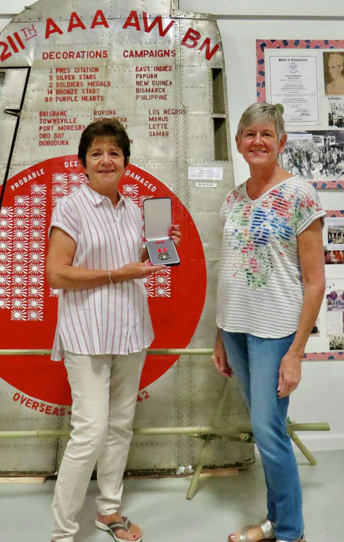 """Kathleen Esposito (left) and West Haven Veterans Museum manager Arlene DeGrand Painter standing in front of tail wing from Japanese fighter plane shot down over the Philippines by the """"Branford Battery Boys"""" in February 1942 at the West Haven Veterans Museum. Esposito is holding the Bronze Star of her uncle, Sgt. John Hurlburt"""