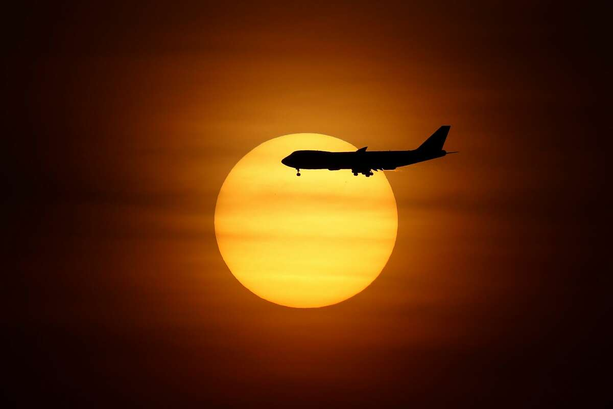 FILE - A commercial airplane makes a descent towards Changi International Airport at sunrise on September 26, 2021 in Singapore. (Photo by Suhaimi Abdullah/NurPhoto via Getty Images)