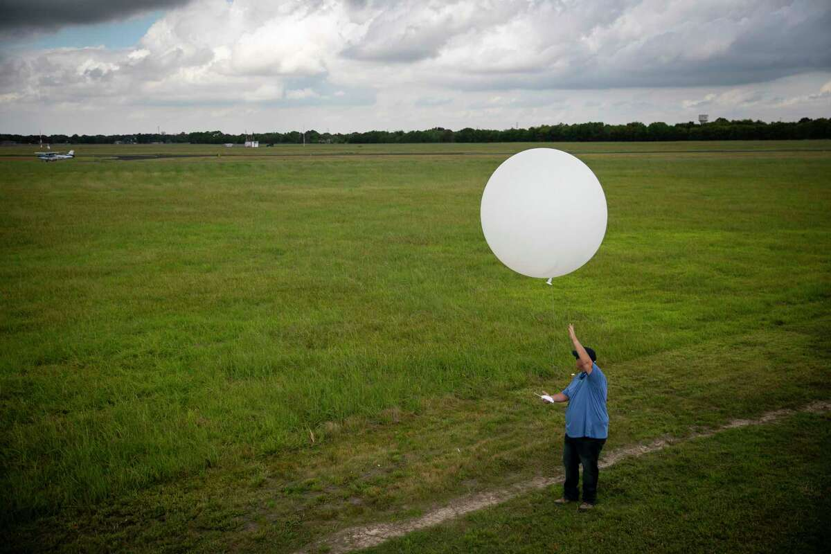 """David Oaks prepares to release a weather balloon with a radiosonde sensor at the Atmospheric Radiation Measurement (ARM) user facility in La Porte, TX, on Monday, Sept. 27, 2021. Oaks is the lead """"TRACER"""" technician (TRacking Aerosol Convection interactions ExpeRiment) at the station."""